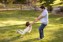 Father Swinging Daughter By Her Arms In Park Stock Images