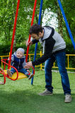 Father swinging his baby. Father and son on a swing in a park. Happy father pushing toddler boy on swing in playground. Smiling little boy sitting on a swing Stock Image