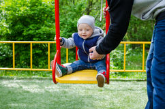 Father swinging his baby. Father and son on a swing in a park. Happy father pushing toddler boy on swing in playground. Smiling little boy sitting on a swing Stock Photography