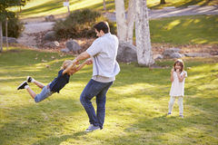 Father Swinging Son By His Arms In Park As Daughter Watches royalty free stock images