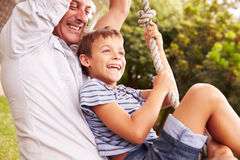 Father swinging with son at a playground Stock Image