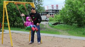 Father swings little pretty girl on swing at playground. In cloudy day stock video footage