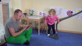 Father with tablet and cute girl hoover floor with vacuum cleaner at home stock footage