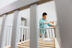 Father with tablet pc and ruler measuring baby bed stock photo