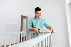 Father with tablet pc and ruler measuring baby bed stock photos