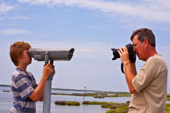 Father takes a picture of his son looking thru a telescope Royalty Free Stock Photos