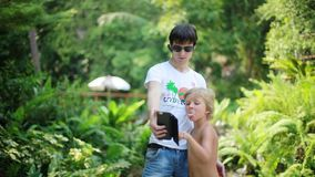 Father wearing sunglasses takes pictures with a photo camera with his son in front of a waterfall. Thailand. Koh Samui stock footage
