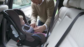 Father Taking Baby Out Of Car Seat stock footage