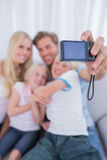 Father taking family picture. Father taking picture of his family in the living room Stock Photos