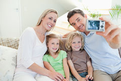 Father taking family picture on sofa Royalty Free Stock Image