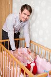 Father taking his baby girl in hands from bed Royalty Free Stock Photos