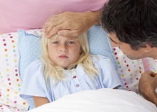 Father taking his daughter's temperature in bed Royalty Free Stock Photography