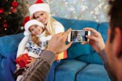 Father taking photo of his cheerful wife and daughter in Santa`s Stock Photos