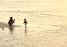 Father taking photo of son on beach Royalty Free Stock Images