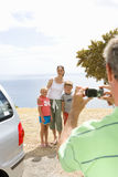 Father taking photograph of mother with son and daughter (6-10) on beach, smiling Stock Image