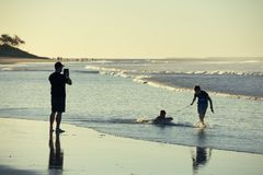Father taking photos of kids with tablet. Silhouette shot of a father taking a photo of his children playing with a boogie board at the beach. He is using his Royalty Free Stock Photography