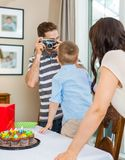 Father Taking Picture Of Birthday Boy And Woman Stock Images
