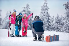 Father taking picture of family standing in snow on the mountain Royalty Free Stock Photography