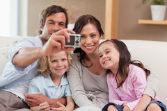 Father taking a picture of his family. In the living room Stock Photography