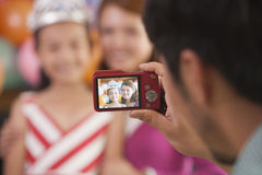 Father Taking a Picture of Mother and Daughter on Daughter's Birthday Royalty Free Stock Images