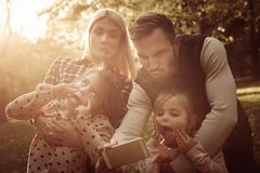 Father taking self picture of family in meadow. stock image