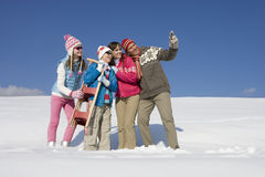 Father taking self-portrait of family standing in snow Stock Photography