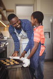 Father taking tray of fresh cookies out of oven with son in kitchen Royalty Free Stock Photos