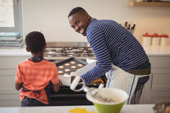 Father taking tray of fresh cookies out of oven with son in kitchen Royalty Free Stock Photography
