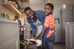 Father taking tray of fresh cookies out of oven with son in kitchen Royalty Free Stock Photo