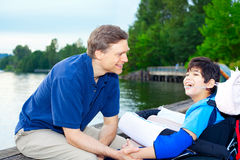 Father talking with disabled son in wheelchair at lake Royalty Free Stock Photos
