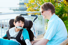 Father talking with disabled son in wheelchair outdoors Stock Image