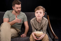 Father talking and gesturing to little son sitting on sofa with popcorn in bowl. Family problems concept royalty free stock photos