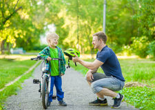 Father talking with his son riding a bicycle Stock Image
