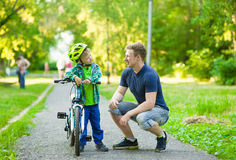 Father talking with his son riding a bicycle Royalty Free Stock Photo