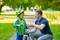 Father talking with his son teaching him to ride a bike Royalty Free Stock Images