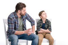 Father talking with little son sitting on chair with crossed arms and looking up. Family problems concept Stock Photography