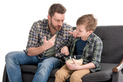 Father talking with son sitting on sofa and eating popcorn from bowl. Family problems concept Royalty Free Stock Photo