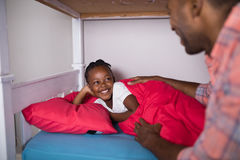 Father talking to daughter lying on bed at home Royalty Free Stock Image