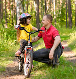 Father talking to his daughter, which teaches to ride a bike Stock Images