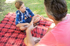 Father talking to son at picnic in park Royalty Free Stock Photo