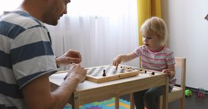 Father teach his child to play chess at home stock video