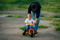 Father teach his young son to drive a bicycle Stock Images