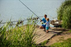 Father teach small son to fish in freshwater. Man and child boy fishing with rods on wooden pier. Fishing, angling, activity, adventure. Vacation, hobby stock photos