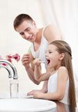 Father teachers his daughter to clean teeth. In bathroom Royalty Free Stock Images