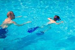 The father teaches the child to swim Stock Photos