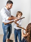 Father teaches children to play bamboo flute. Father teaches son and daughter to blow bamboo flute royalty free stock photo