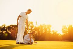 A man teaches a girl to play golf. girl puts a ball on a stand, man holds a stick Royalty Free Stock Images