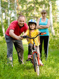 Father teaches his daughter to ride a bike Royalty Free Stock Photos