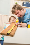 Father teaches his son carpentry in  garage Stock Image