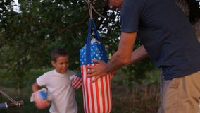 Father teaches his son to boxing. Training outdoor in the garden near the house with a pear with usa symbols. Fathers